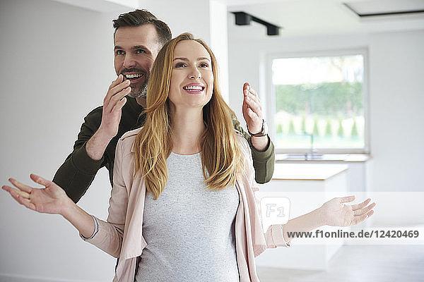 Man surprising woman in empty flat Man surprising woman in empty flat