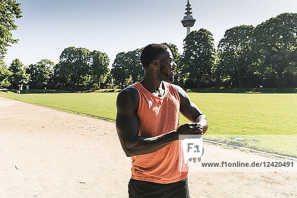 Young athlete in training on sports field taking the time on his smartwatch
