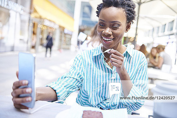 Portrait of smiling woman using earphones and smartphone at pavement cafe Portrait of smiling woman using earphones and smartphone at pavement cafe