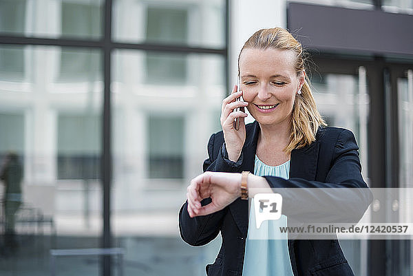 Portrait of smiling businesswoman on the phone checking the time