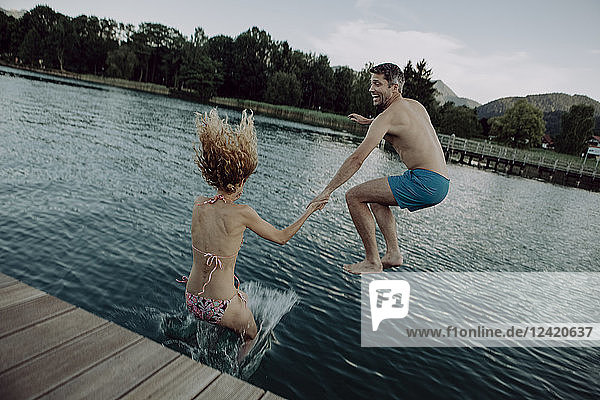 Happy couple jumping hand in hand into swimming lake