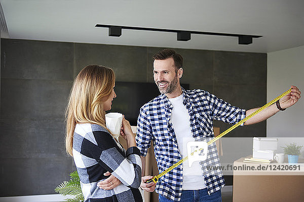 Couple moving into new flat measuring with tape measure