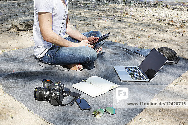 Man sitting on blanket at a beach using tablet