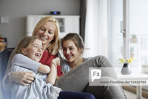 Happy mother and daughters having fun at home