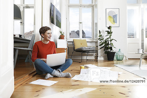Woman sitting cross-legged on floor of her home  using laptop
