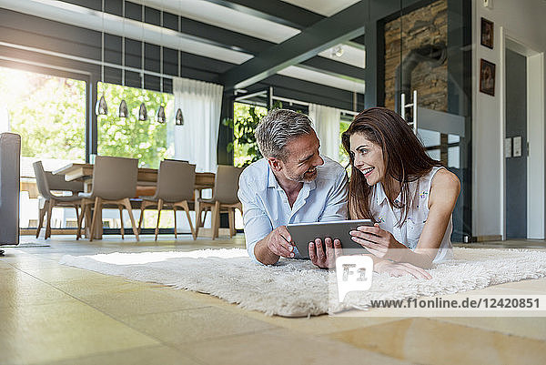 Happy couple lying on carpet at home sharing a tablet