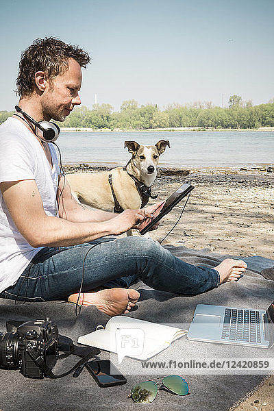 Man with dog sitting on blanket at a river using tablet