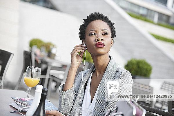 Portrait of businesswoman using earphones outdoors