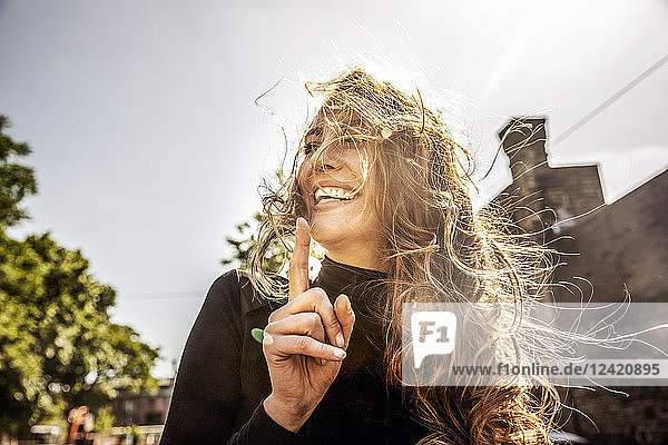 Portrait of laughing woman with blowing hair
