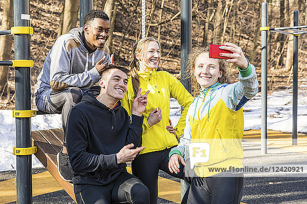Happy friends taking a selfie at fitness equipment in a park