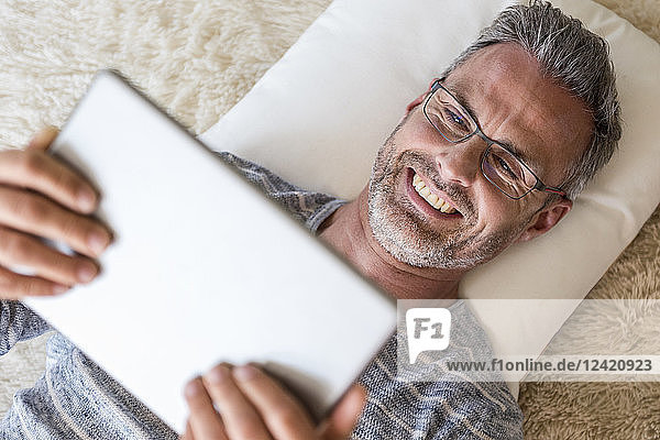 Mature man lying on pillow using a tablet