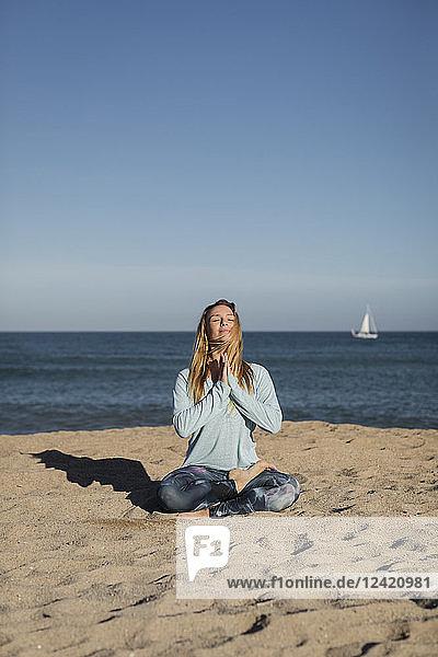 Woman doing yoga on the beach  lotus position