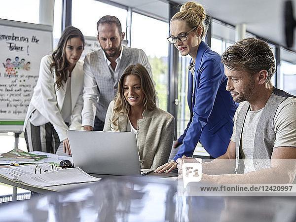Business people having a workshop sharing laptop