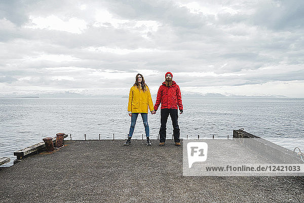 Iceland  North of Iceland  young couple standing hand in hand on jetty