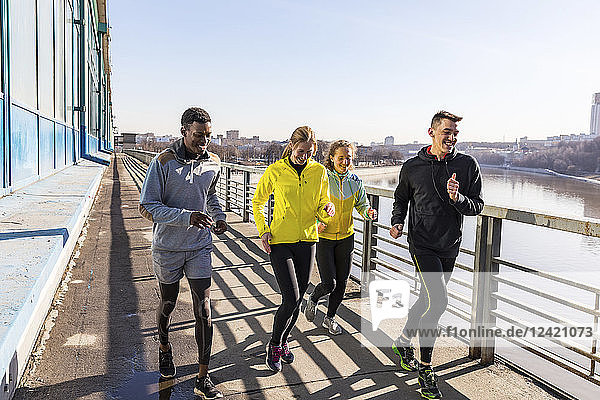 Friends running on a bridge in the city