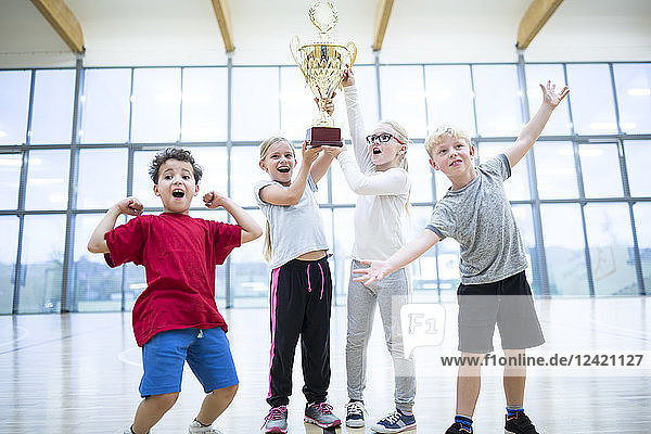 Happy pupils holding trophy in gym