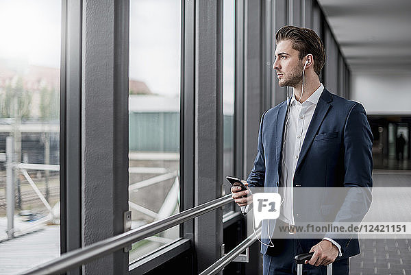 Young businessman in a passageway with cell phone  earbuds and rolling suitcase