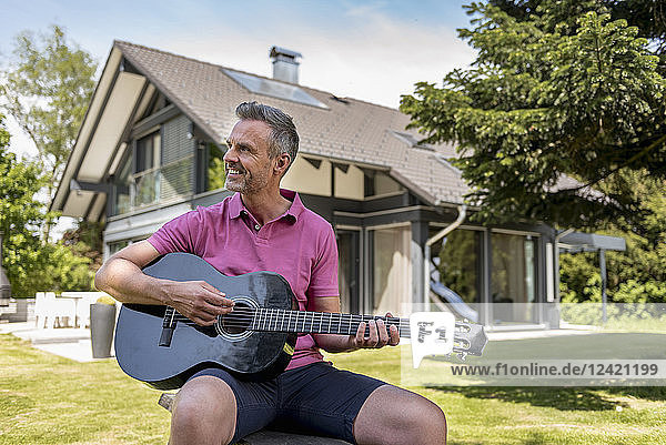 Smiling mature man sitting in garden of his home playing guitar