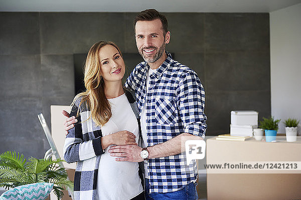 Portrait of happy man and pregnant woman moving into new flat