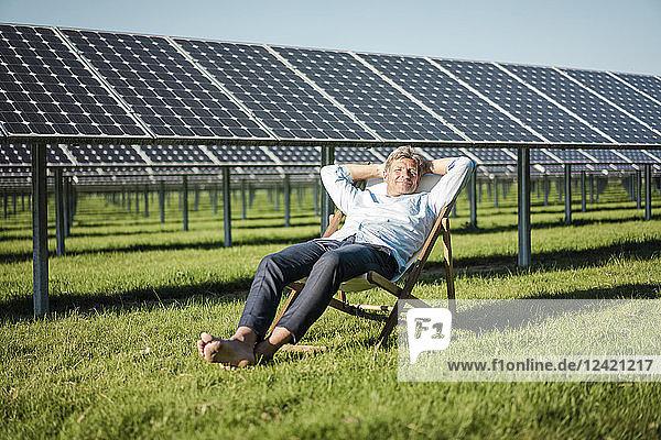 Mature man sitting in sun lounger  solar plant