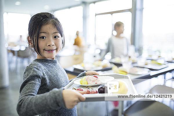 Portrait of smiling schoolgirl carrying tray in school canteen