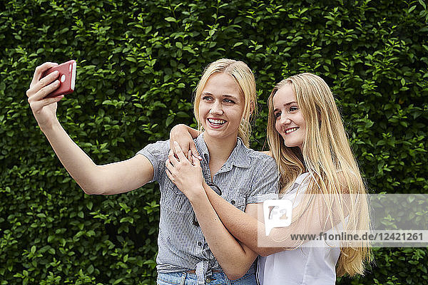 Two happy young women taking a selfie at a hedge