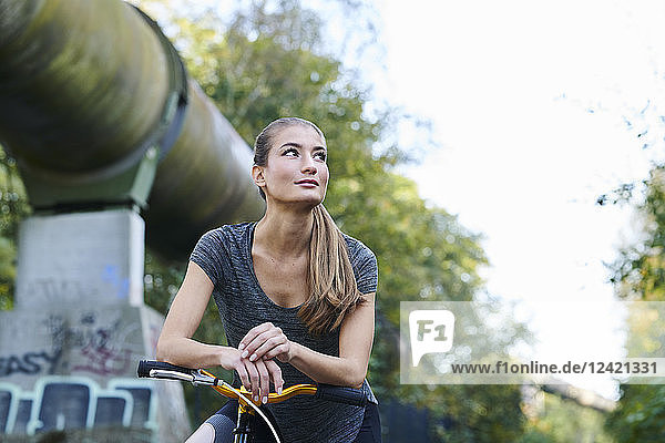 Portrait of sportive young woman with bicycle looking sideways