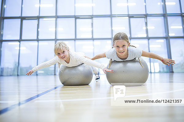 Portrait of smiling schoolgirls balancing on gym balls in gym class