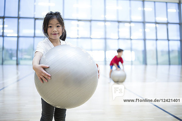 Portrait of smiling schoolgirl holding gym ball in gym class