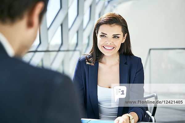 Businesswoman smiling at businessman in modern office