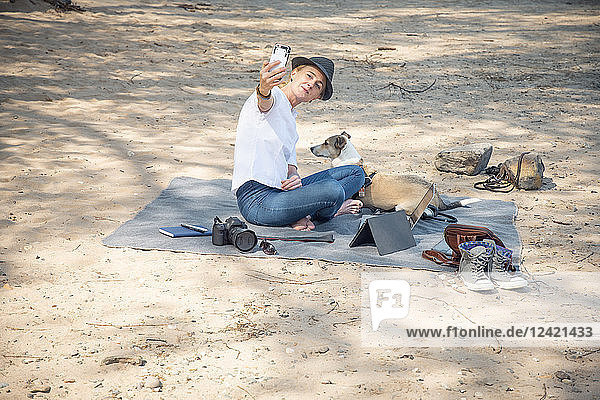 Woman sitting on blanket on beach with dog taking a selfie