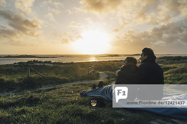 France  Brittany  Landeda  couple sitting at the coast at sunset