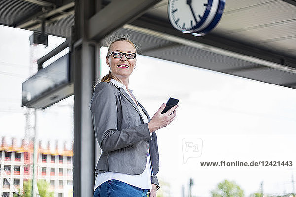 Portrait of smiling businesswoman with cell phone waiting at platform