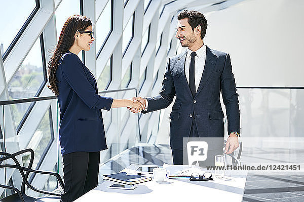 Businesswoman and businessman shaking hands in modern office