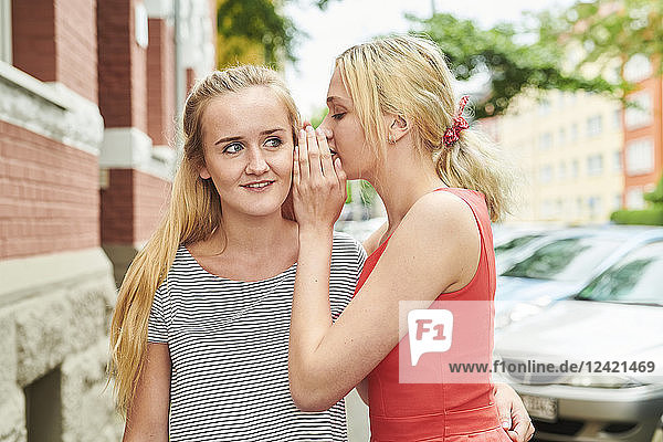 Two young women in the city whispering