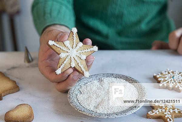 Man's hand holding homemade Christmas Cookie  close-up