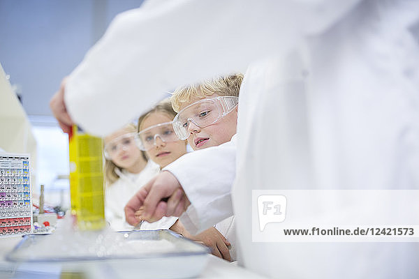 Pupils in science class watching teacher experimenting