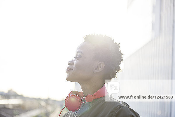 Profile of young woman with red headphones at backlight Profile of young woman with red headphones at backlight