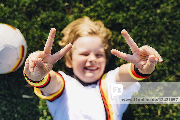 Boy in German soccer shirt lying on grass  making victory sign