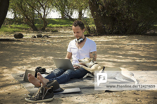 Man with dog sitting on blanket at a beach using laptop