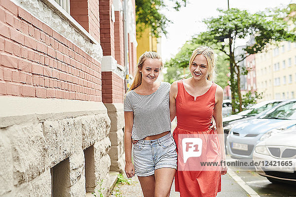 Two happy young women walking in the city together