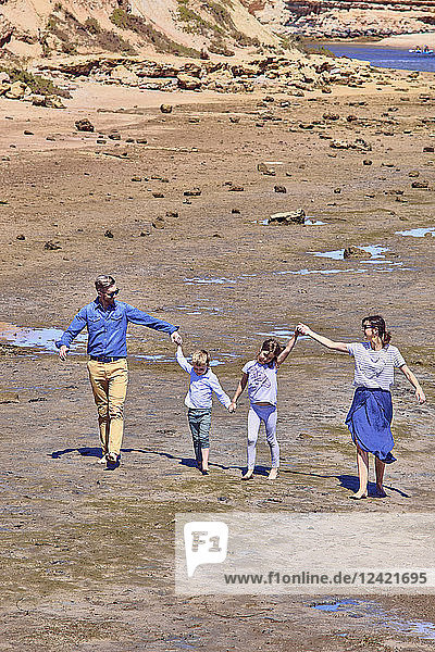 Australia  Adelaide  Onkaparinga River  happy family walking together hands in hands at beach