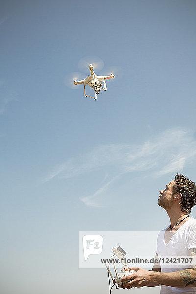 Man flying drone under blue sky
