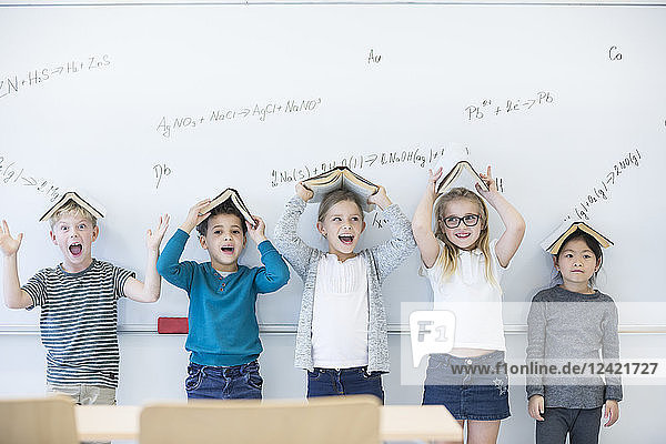 Happy pupils with books above their heads standing at whiteboard with formulas in class