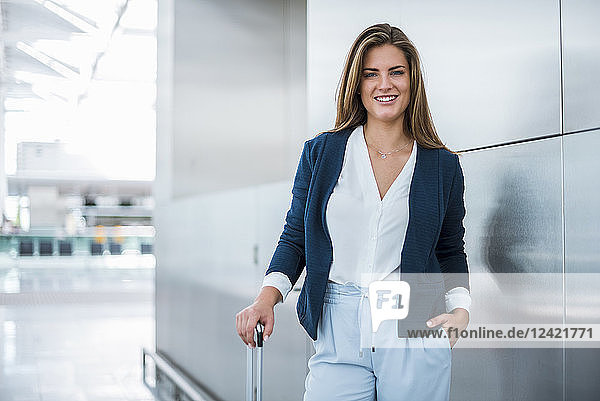 Portrait of smiling young businesswoman with luggage