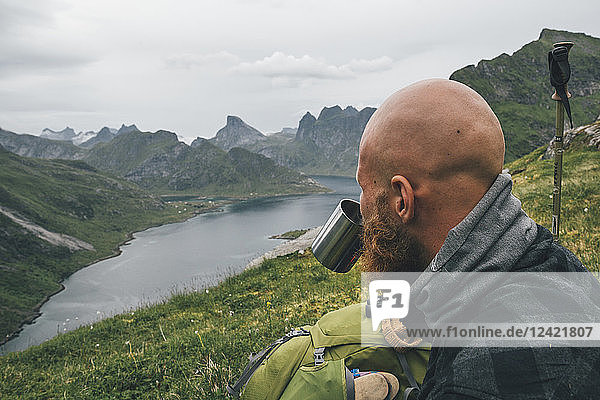 Norway  Lofoten  Moskenesoy  Man looking at view  drinking from tin cup