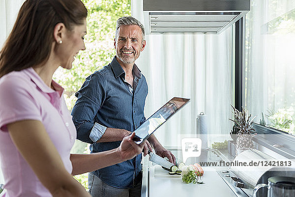 Happy couple in kitchen at home cooking and using a tablet