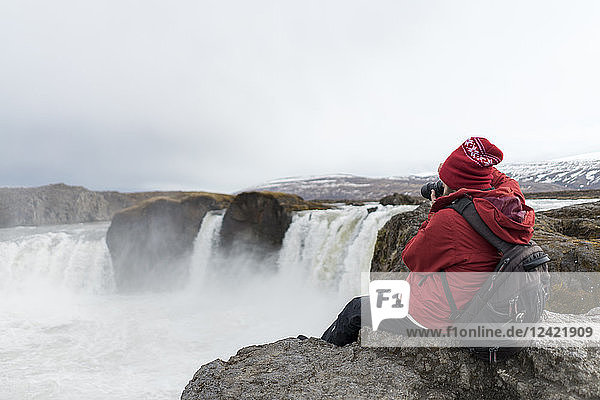 Iceland  North of Iceland  young man photographing waterfall