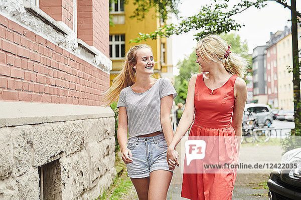 Two happy young women walking hand in hand in the city