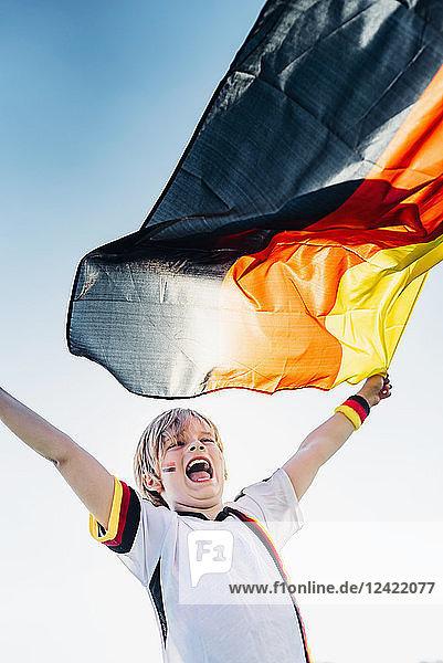 Boy  enthusiastic for soccer world championship  waving German flag